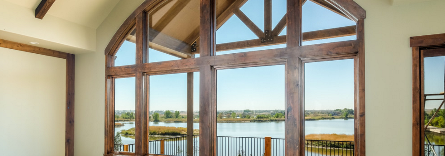 Great room looking out onto a beautiful view of the lake. Large fixed glass windows and exposed wood rafters.